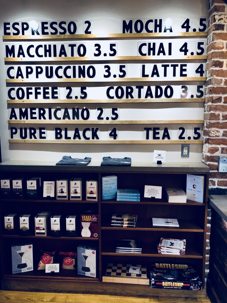 coffee menu on wall over top of black bookshelves