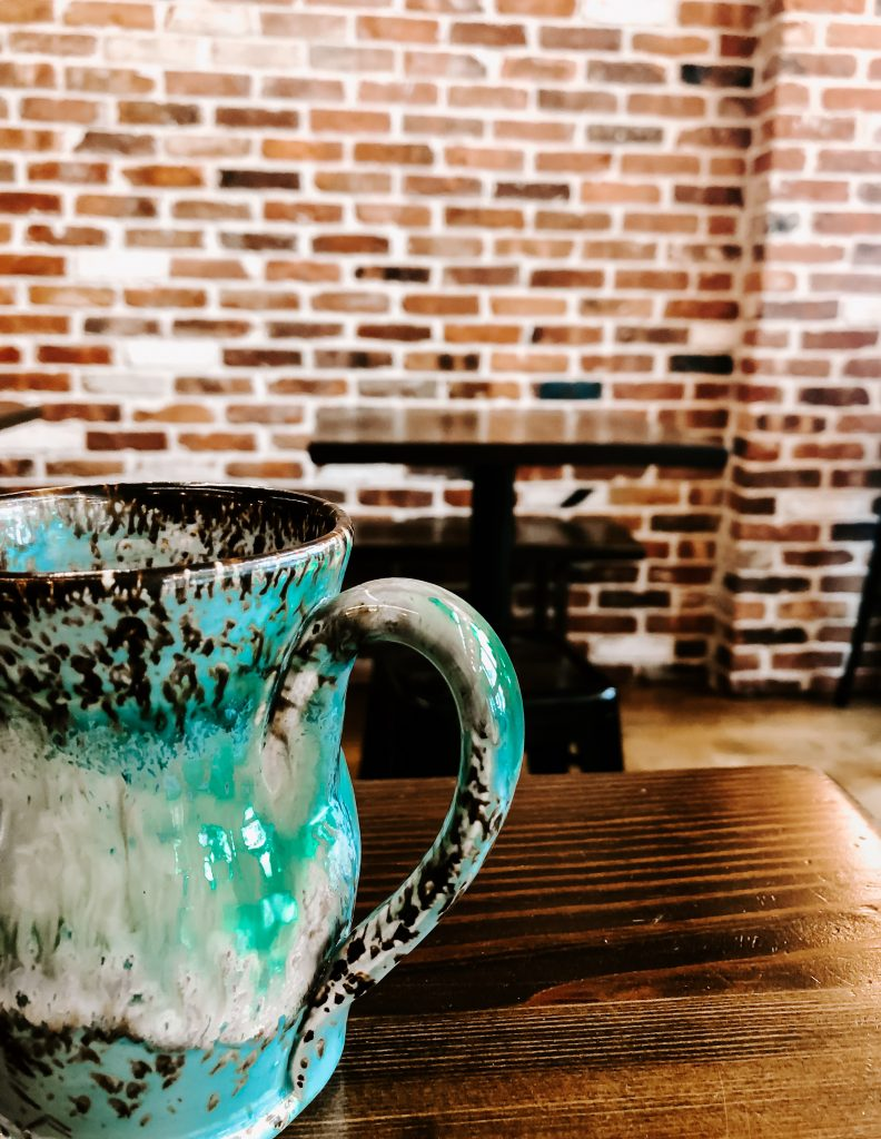 bright teal coffee mug in front of exposed brick wall