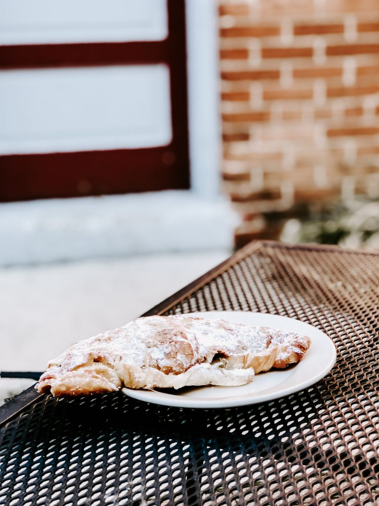 Iron table with large croissant in front of a brick wall