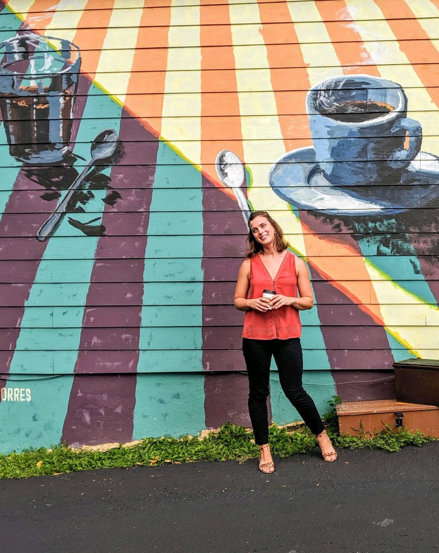Nina stands in front of coffee mural holding a cup