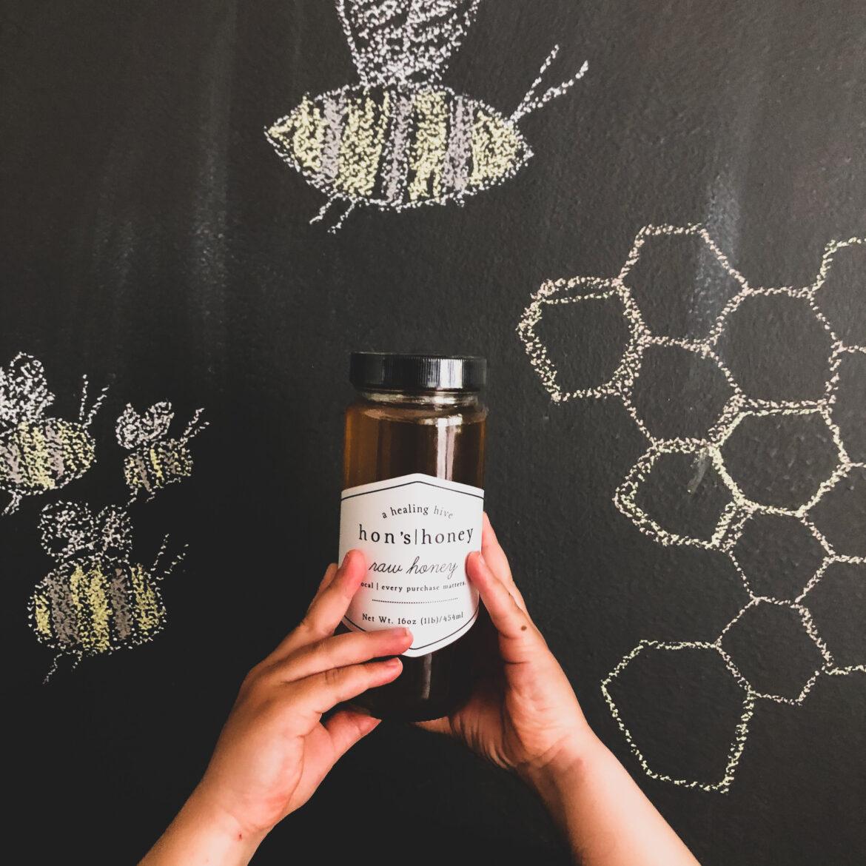 honey jar in front of black background
