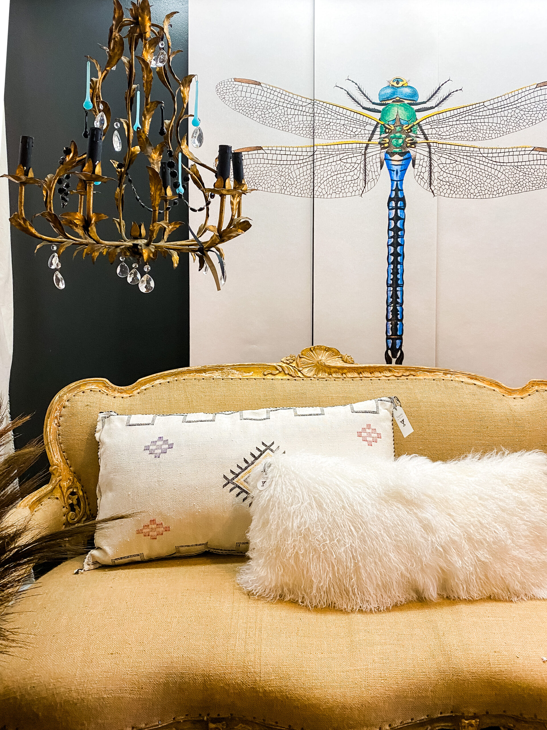 vintage cream couch in front of a vivid 5 foot tall dragonfly mural next to a vintage chandelier